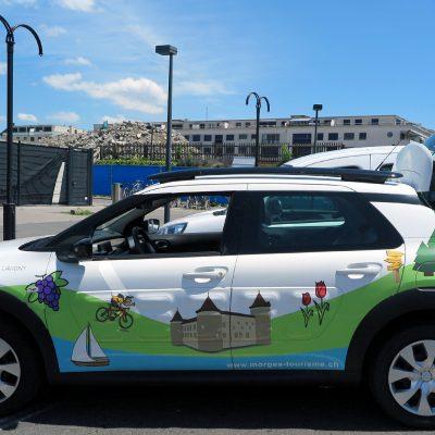 Mobil in Morges: Das Auto von Morges Tourismus fährt bunt bebildert vor.